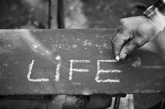 The elders respect life. An old man wrote with a chalk on a blackboard the most beloved word Stock Photography