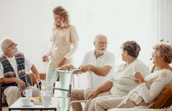 Elders spending time in the common room of the care home stock images