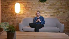 eldery白种人特写镜头画象女性使用电话微笑的放松,当坐在舒适时的沙发 股票录像