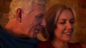 eldery愉快的夫妇特写镜头射击使用在一栋舒适公寓休息和放松的户内膝上型计算机的 影视素材
