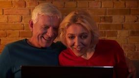 eldery愉快的夫妇特写镜头射击使用微笑充满喜悦的膝上型计算机的坐长沙发户内在一栋舒适公寓 股票录像