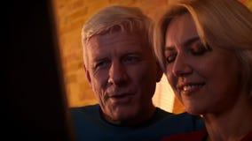 eldery愉快的夫妇特写镜头射击使用微笑的膝上型计算机的快乐地坐长沙发户内在舒适 影视素材