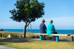 Eldery couple rest and look at scenic ocean view on bench seat a Royalty Free Stock Image