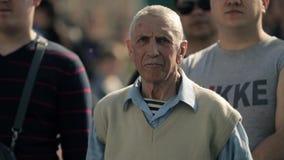 Eldery granfatherdans till musik bland folkmassan av folk på sommarhändelse arkivfilmer