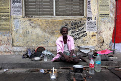 An eldery homeless man sitting on the street. With kitchenware and water for cooking, He used this area as a home. Pondicherry-Tamil Nadu, India-26 April 2012 Royalty Free Stock Photo