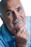 Eldery mężczyzna z kierowniczy odpoczywać na rękach Obrazy Stock