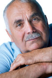 Eldery man with head resting on arms Royalty Free Stock Image