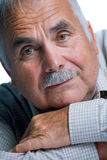 Eldery man with head resting on arms Stock Image