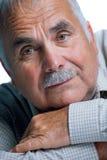 Eldery man med huvudet som vilar på armar Fotografering för Bildbyråer