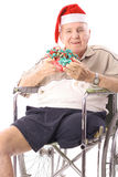 Eldery man in wheelchair celebrating christmas ver. Shot of an eldery man in wheelchair celebrating christmas vertical Royalty Free Stock Photo