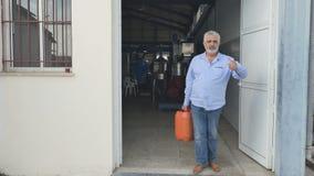 Eldery-Mann, der mit Kanister am Eingang zur Fabrik steht stock video footage