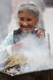 Eldery woman burning incense, Kathmandu Royalty Free Stock Images