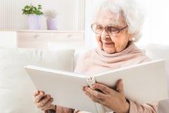 Free Eldery Woman Looking Photo Album Stock Photos - 148343893