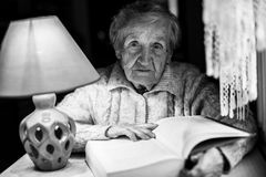 An eldery woman reads a book under a table lamp at night. Stock Images