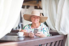 An eldery woman sitting in the coffe house Stock Photo