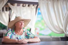 An eldery woman sitting in the coffe house. Royalty Free Stock Image