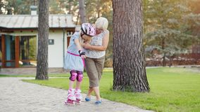 Eldery woman teach the girl to skate on roller skates. Active senior people