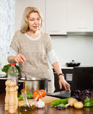 Eldery woman using notebook while cooking soup Royalty Free Stock Photo