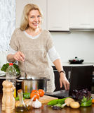 Eldery woman using notebook while cooking vegetables Stock Photography
