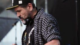 Elderygrootvader DJ bij het paneel van DJ op stadium De avond van de zomer stock footage