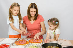 Eldest daughter helps her mother cook a pizza, and the youngest is watching them Stock Photo
