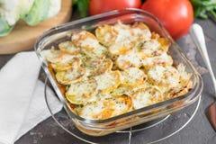 Eldfast form från potatisen med gräddfilsås, grönsaker, tomatoe Royaltyfri Foto