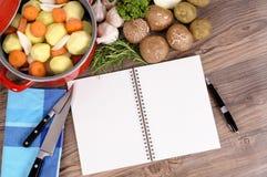 Eldfast formmaträtt med grönsaker och kokboken på köksbordet, kopieringsutrymme Royaltyfri Bild