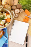Eldfast formsoppgryta med organiska grönsaker på kökskärbräda med den tomma receptboken eller kokboken, kopieringsutrymme Royaltyfri Foto