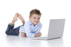 a criança olha o computador Fotografia de Stock Royalty Free