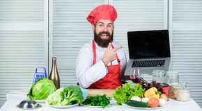 Elearning concept. Chef laptop read culinary recipes. Culinary school. Hipster in hat and apron learning how to cook. Online. Culinary education online. Man stock photo