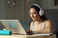 Elearning del estudiante que mira tutoriales en línea en la noche Imágenes de archivo libres de regalías