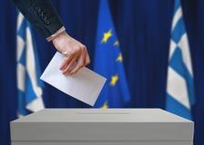 Elección en Grecia El votante lleva a cabo la votación antedicha disponible del voto del sobre Imágenes de archivo libres de regalías