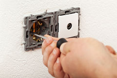 Electician hands installing electical wall sockets. Electrician hands installing electical wall sockets - closeup, focus on the fixture Stock Photo