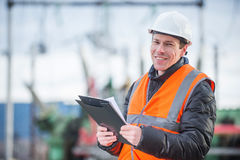 Electician with substation on the background. Handsome electrical engineer holding papers in substation Royalty Free Stock Photo