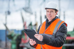 Electician with substation on the background. Handsome electrical engineer holding papers in substation Royalty Free Stock Image