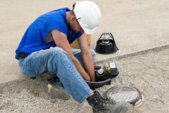 Electician Wiring Spotlight. Electrician sitting on pavement while wiring spotlight at construction site Stock Images
