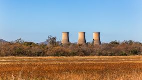 Electicity Power Station Cooling Towers Countryside. Electricity power station with three cooling towers structures in rural farming countryside a panorama photo royalty free stock photo