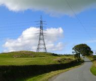 Electicity pylon alongside a country road. An electricity pylon on a hillside alongside a quiet country road, and beneath a symbolic grey cloud royalty free stock image
