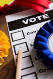 Election Ballot Paper With Rosettes Of Political Parties. Still Life Of Election Ballot Paper With Rosettes Of Political Parties stock photography