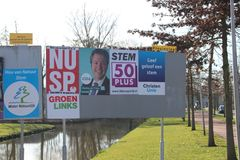 Election campaign posters on public billboards pasted by parties themselves in nIeuwerkerk aan den Ijssel in the Netherlands. Election campaign posters on royalty free stock photo