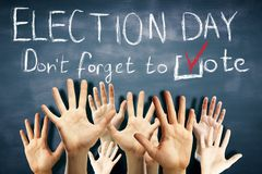 Election day concept. Many waving hands on chalkboard background with text. Election day concept Royalty Free Stock Photography