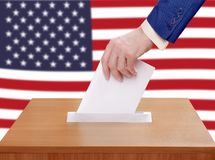 Election Day in the United States of America. A person votes by throwing a ballot in the ballot box Stock Photo