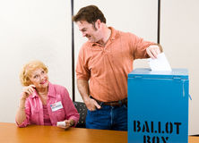 Election Day in USA. Male suburban voter casting his ballot while an election volunteer looks on Royalty Free Stock Photo