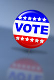 Election day vote button. With reflection on a table Royalty Free Stock Images