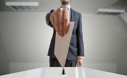 Election and democracy concept. Voter holds envelope or paper in hand above ballot.  Royalty Free Stock Photos