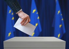 Election in EU. Voter holds envelope in hand above vote ballot. European Union flags in background Stock Photo