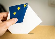 Election in European Union - voting at the ballot box. A hand putting an EU flag vote in the ballot box stock photos