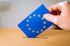 Election in European Union - voting at the ballot box. A hand putting an EU flag vote in the ballot box royalty free stock images