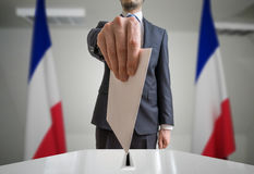 Election in France. Voter holds envelope in hand above vote ball. Wide angle shot.  Royalty Free Stock Image
