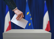Election in France. Voter holds envelope in hand above vote ballot. French and European Union flags in background Royalty Free Stock Image